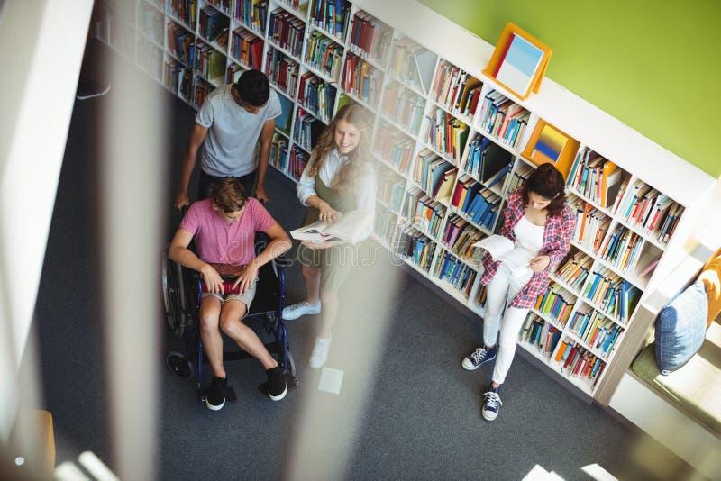 Estudiantes que obran recíprocamente con uno a en biblioteca imagenes de archivo