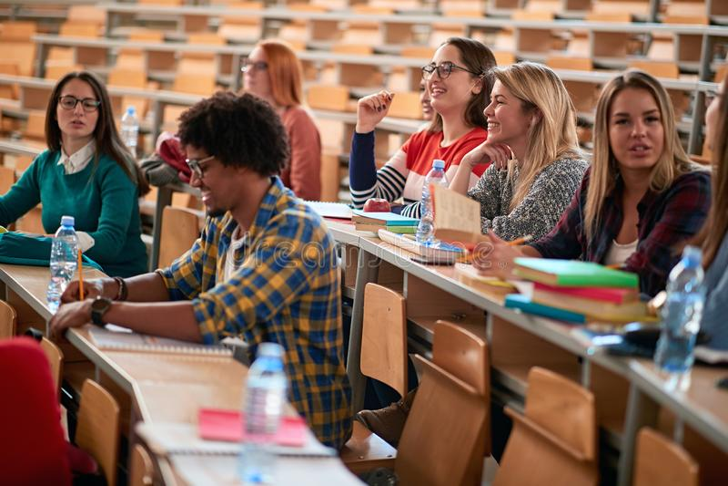 Estudiantes que pasan el tiempo junto en la universidad en auditorio imágenes de archivo libres de regalías
