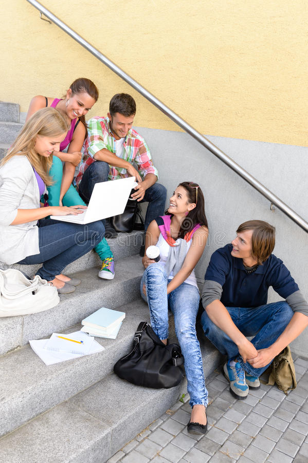 Estudiantes que se divierten con las escaleras de la escuela de la computadora portátil fotos de archivo libres de regalías