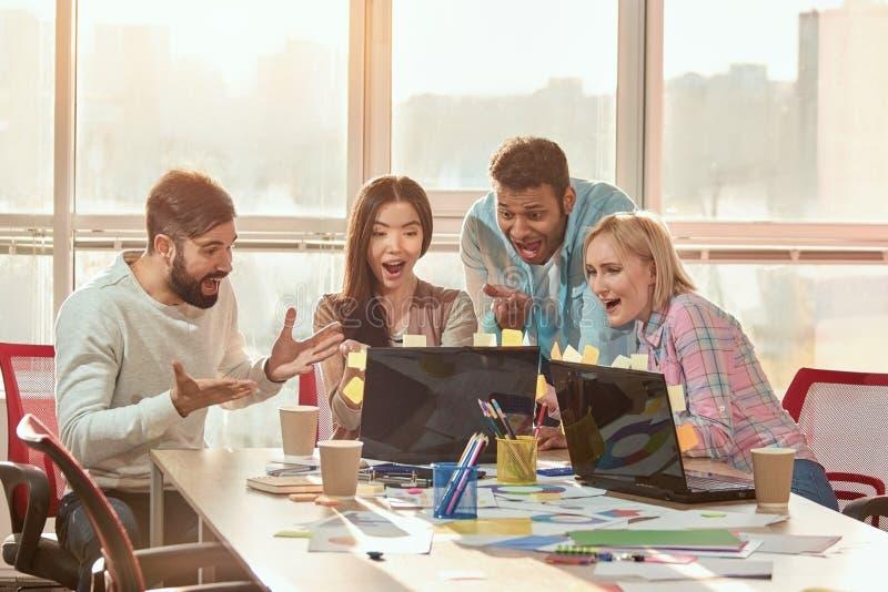 Estudiantes que se divierten y que cooperan y que trabajan con el ordenador fotos de archivo