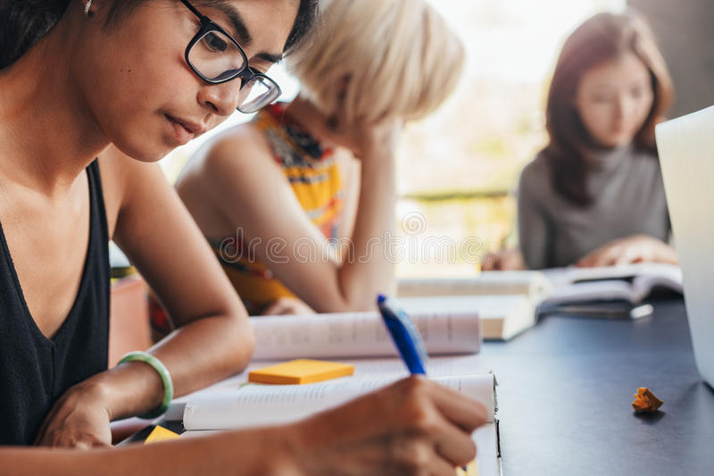 Estudiantes que se sientan en la biblioteca con los libros y estudiar imágenes de archivo libres de regalías