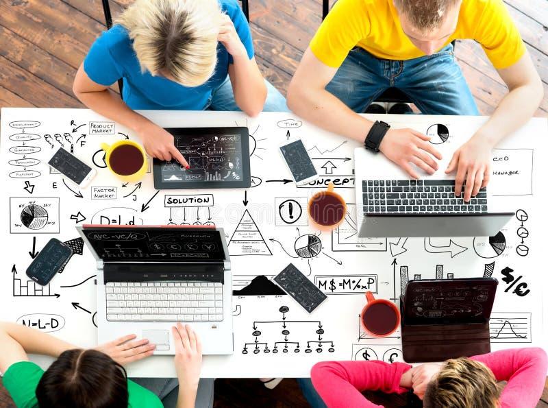 Estudiantes que se sientan en la tabla usando los ordenadores y las tabletas fotografía de archivo libre de regalías