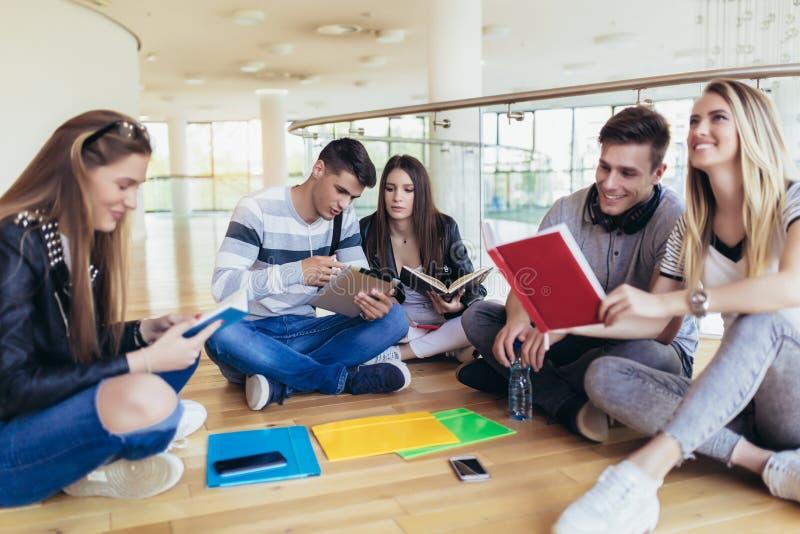 Estudiantes que se sientan en piso en campus y que se preparan junto para los exámenes imagen de archivo