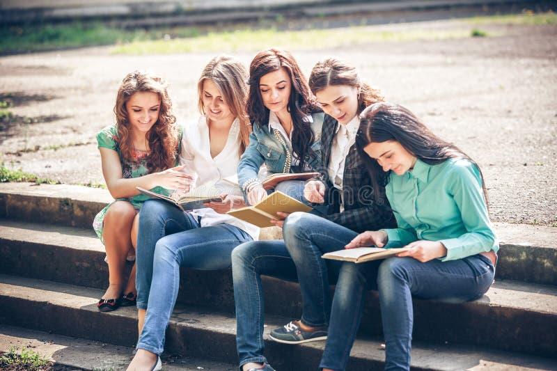 Estudiantes que sientan con los libros en la calle fotografía de archivo libre de regalías