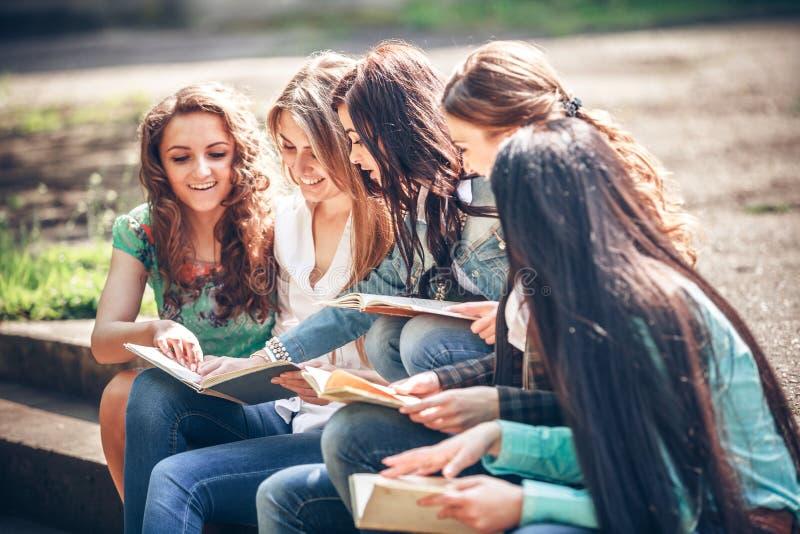 Estudiantes que sientan con los libros en la calle imagen de archivo