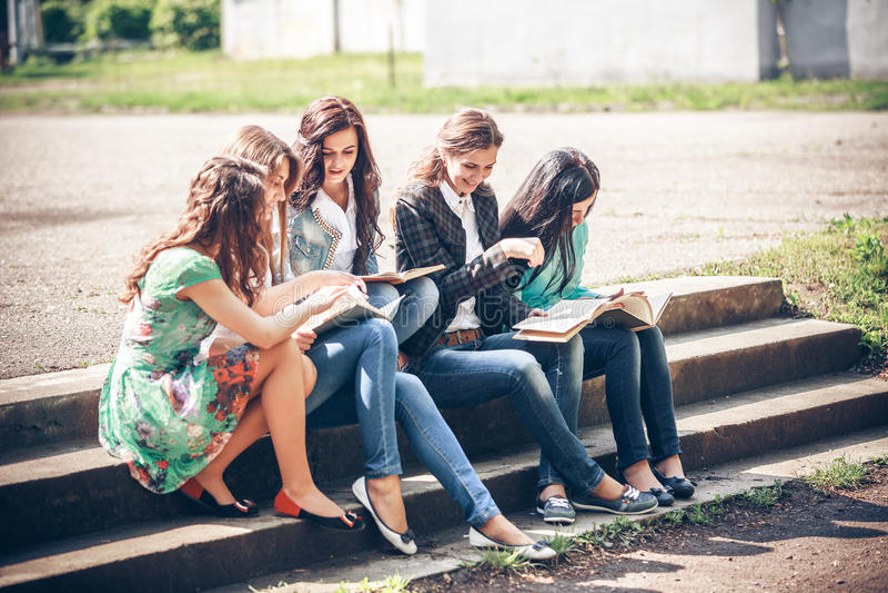Estudiantes que sientan con los libros en la calle fotografía de archivo