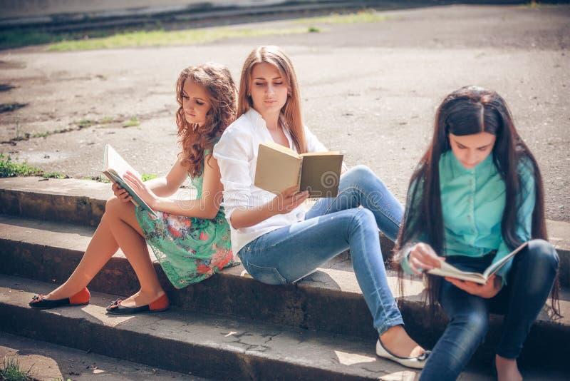 Estudiantes que sientan con los libros en la calle foto de archivo libre de regalías
