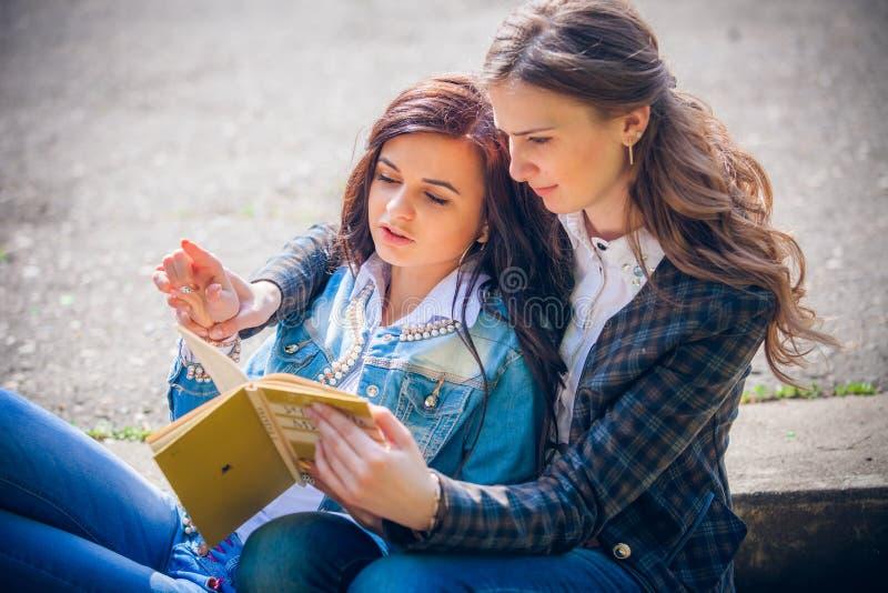 Estudiantes que sientan con los libros en la calle imagenes de archivo