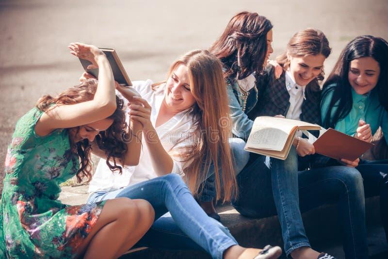 Estudiantes que sientan con los libros en la calle imágenes de archivo libres de regalías
