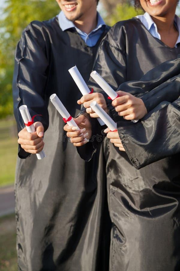 Estudiantes que sostienen los diplomas el día de graduación adentro fotos de archivo