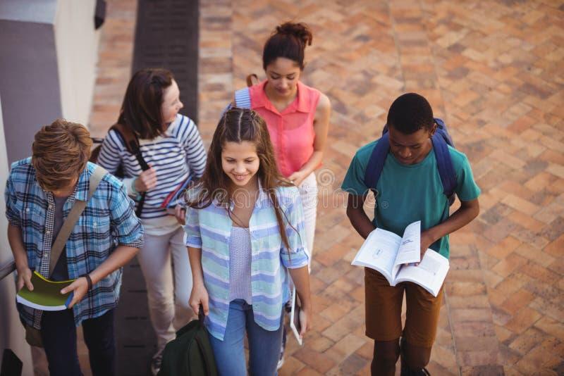 Estudiantes que sostienen los libros y la tableta digital que caminan a través de campus de la escuela fotos de archivo