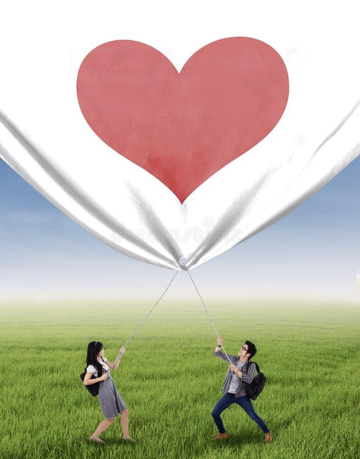 Estudiantes que tiran de la bandera de la tarjeta del día de San Valentín fotos de archivo libres de regalías