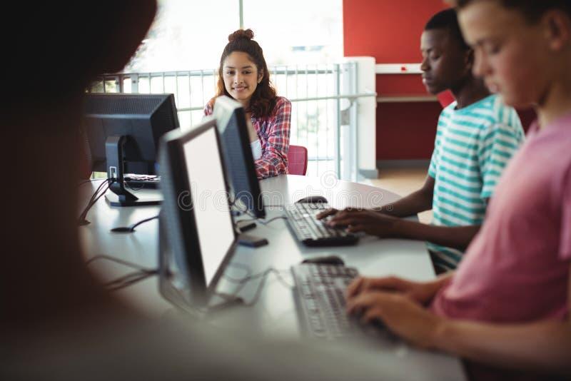 Estudiantes que usan el ordenador en sala de clase imagen de archivo libre de regalías