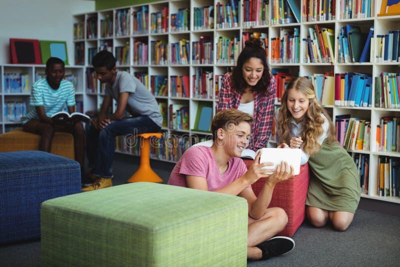 Estudiantes que usan la tableta digital en biblioteca foto de archivo libre de regalías