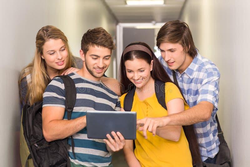 Estudiantes que usan la tableta digital en el pasillo de la universidad imagen de archivo