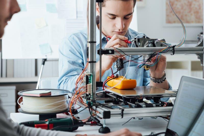 Estudiantes que usan una impresora 3D fotos de archivo libres de regalías