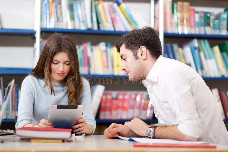 Estudiantes que usan una tableta digital en una biblioteca fotografía de archivo libre de regalías