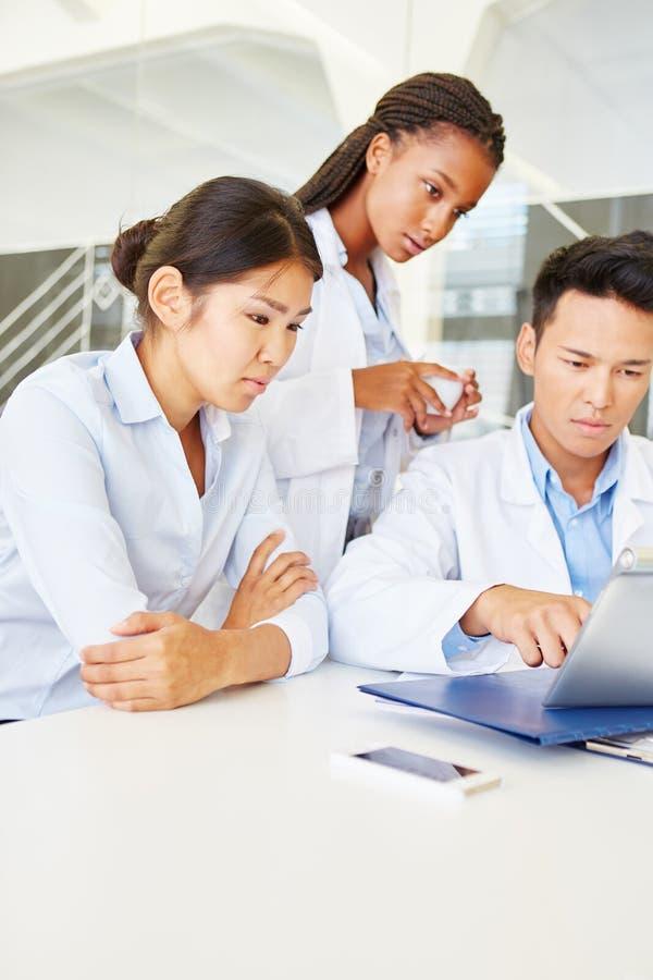 Estudiantes reaserching con la tableta en Facultad de Medicina imagen de archivo