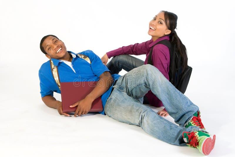 Estudiantes sonrientes asentados - horizontales imagen de archivo libre de regalías