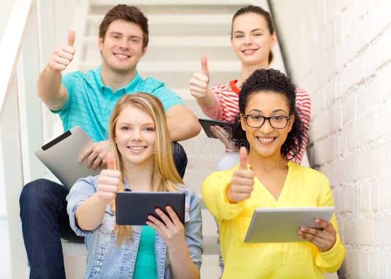 Estudiantes sonrientes con el ordenador de la PC de la tableta imágenes de archivo libres de regalías