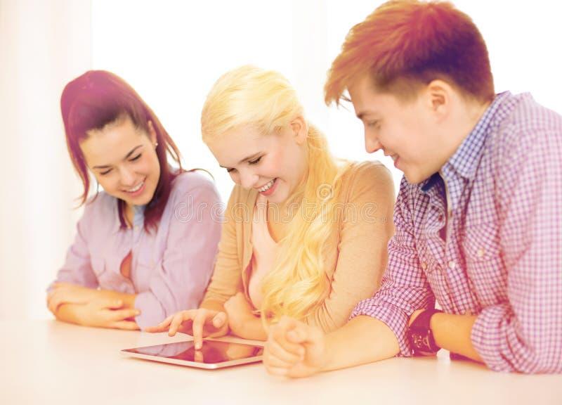 Estudiantes sonrientes con el ordenador de la PC de la tableta en la escuela foto de archivo