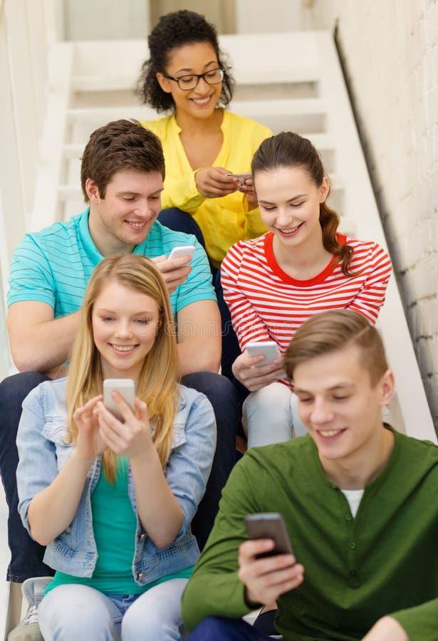 Estudiantes sonrientes con el smartphone que manda un SMS en la escuela fotografía de archivo libre de regalías