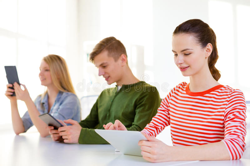 Estudiantes sonrientes con PC de la tableta en la escuela fotos de archivo