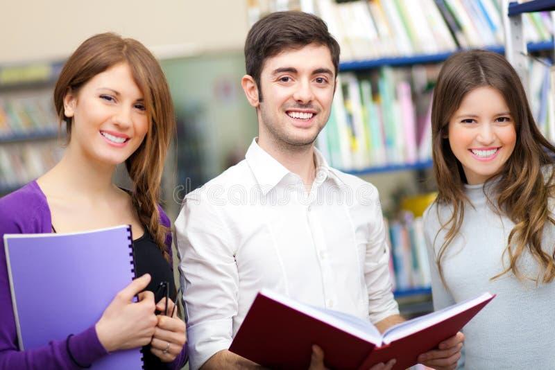 Estudiantes sonrientes en una biblioteca fotografía de archivo libre de regalías