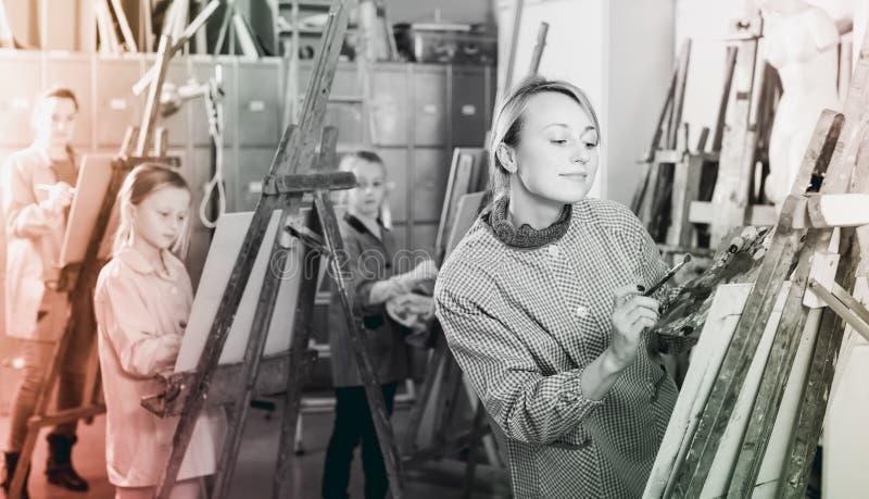 Estudiantes sonrientes que entrenan a habilidades de la pintura durante clase imagen de archivo
