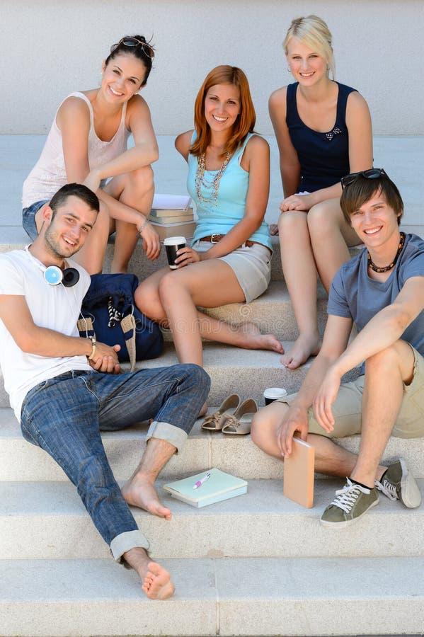 Estudiantes sonrientes que se sientan el verano de las escaleras de la escuela imágenes de archivo libres de regalías