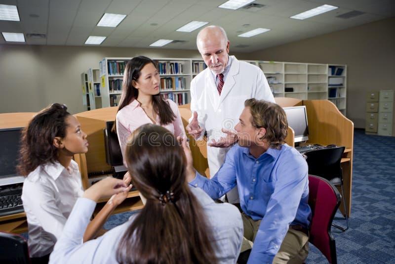 Estudiantes universitarios con el profesor que habla en biblioteca fotos de archivo