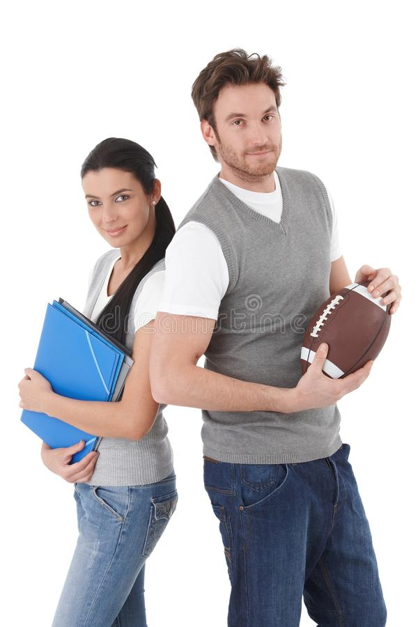 Estudiantes universitarios con las carpetas y la bola de rugbi fotos de archivo libres de regalías