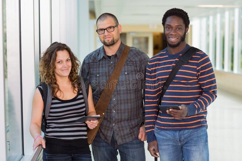 Estudiantes universitarios confiados que se colocan en el pasillo imagen de archivo