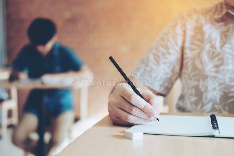Estudiantes universitarios de la prueba final que prueban el examen en universidad imagenes de archivo