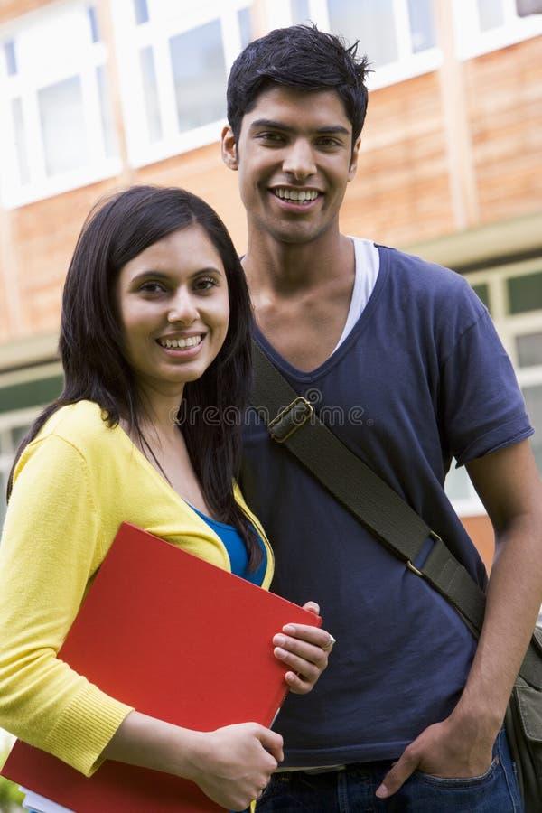 Estudiantes universitarios de sexo masculino y de sexo femenino en campus fotos de archivo