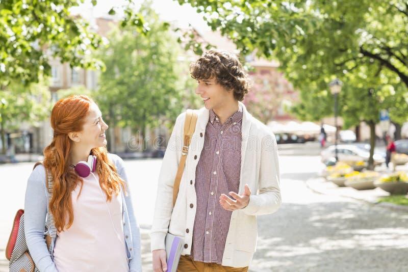 Estudiantes universitarios de sexo masculino y de sexo femenino jovenes que hablan mientras que camina en el sendero imagen de archivo libre de regalías