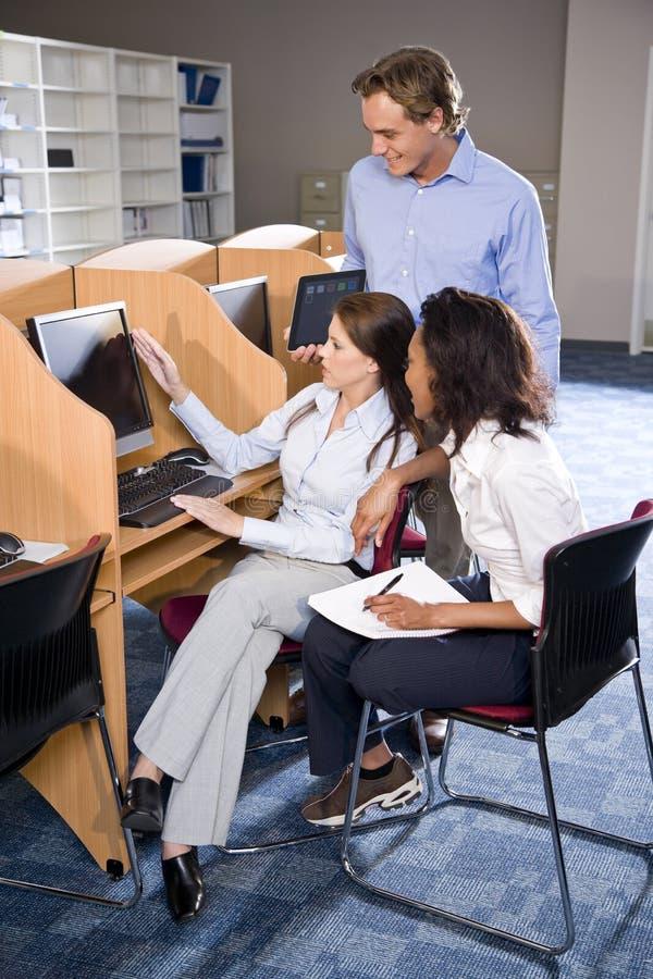 Estudiantes universitarios en estudiar del ordenador de la biblioteca fotografía de archivo