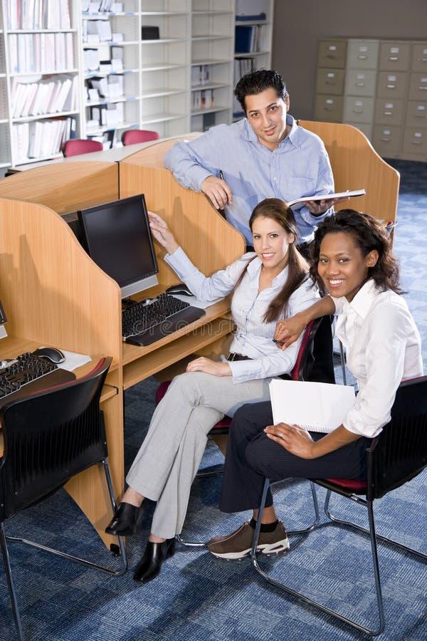 Estudiantes universitarios en estudiar del ordenador de la biblioteca fotos de archivo libres de regalías