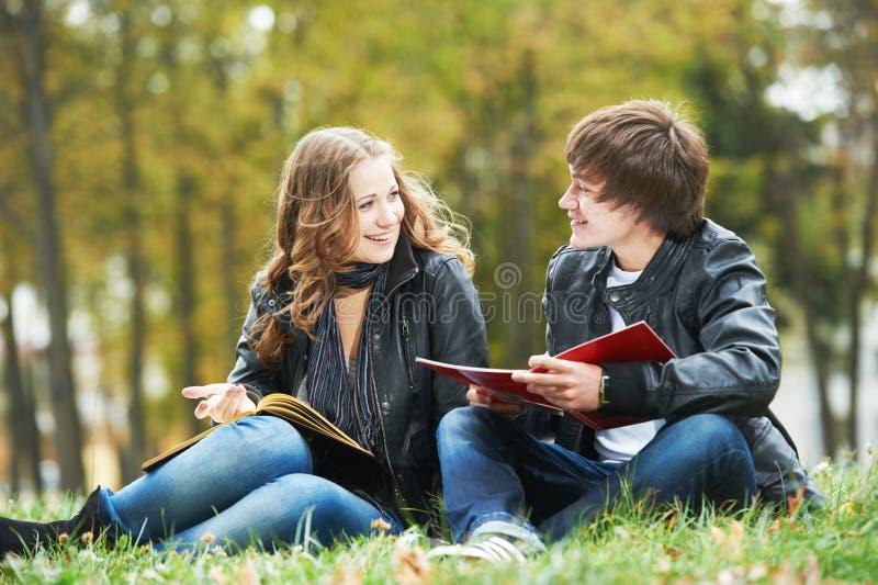 Estudiantes universitarios felices en césped del campus al aire libre fotos de archivo libres de regalías