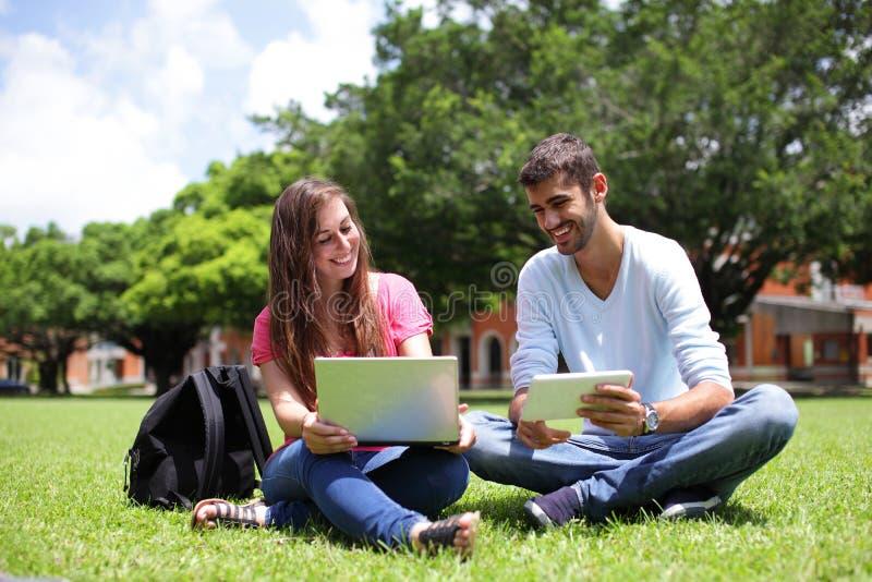 Estudiantes universitarios felices que usan el ordenador fotografía de archivo