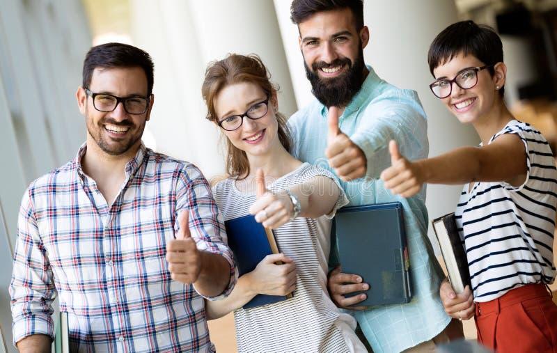 Estudiantes universitarios jovenes felices que estudian con los libros en biblioteca fotografía de archivo libre de regalías
