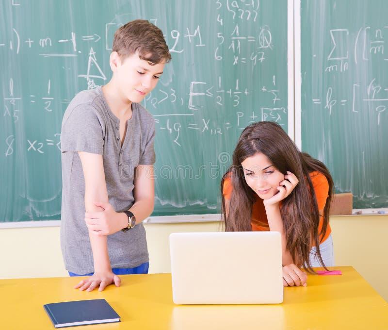 Estudiantes universitarios jovenes que usan el ordenador portátil imagen de archivo libre de regalías