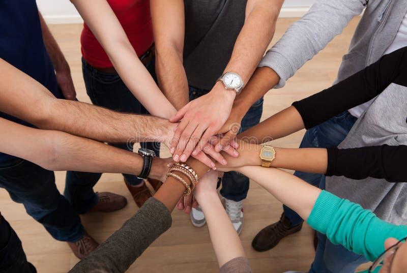 Estudiantes universitarios multiétnicos que apilan las manos imagenes de archivo