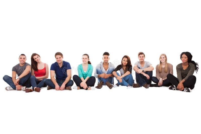 Estudiantes universitarios multiétnicos que se sientan en fila imagenes de archivo