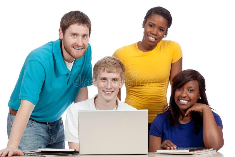 Estudiantes universitarios multiculturales alrededor de un ordenador fotos de archivo