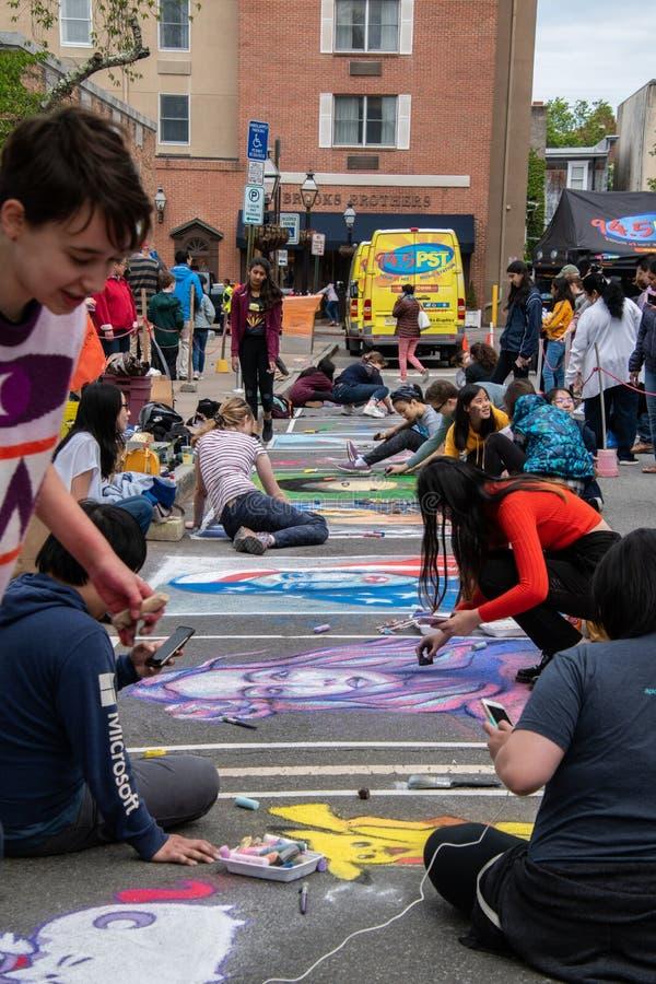 Estudiantes universitarios multiculturales jovenes que dibujan murales con tiza en una calle del asfalto foto de archivo libre de regalías