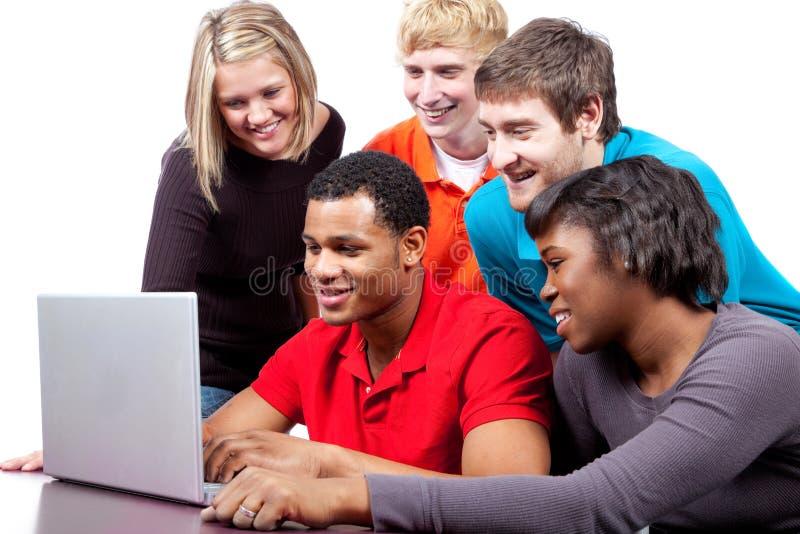 Estudiantes universitarios multirraciales por un ordenador imagen de archivo libre de regalías