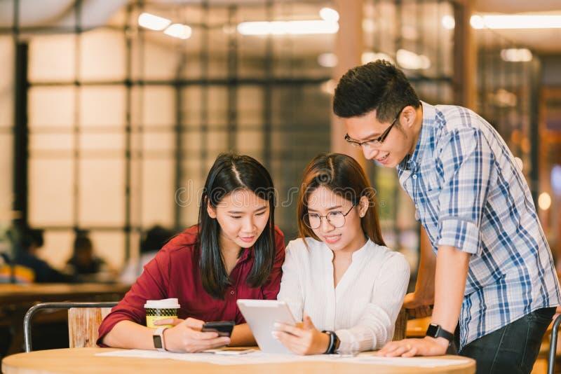 Estudiantes universitarios o compañeros de trabajo asiáticos que usan la tableta y el smartphone digitales junto en la cafetería imagen de archivo libre de regalías