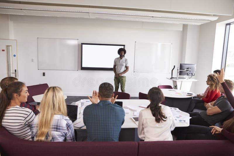 Estudiantes universitarios que asisten a conferencia en campus fotos de archivo libres de regalías