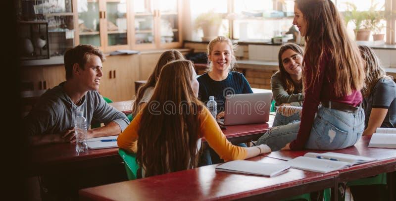 Estudiantes universitarios que charlan durante rotura en clase fotografía de archivo